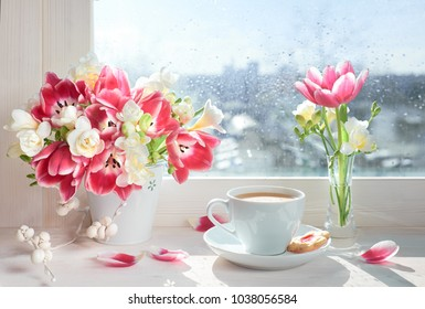 Cup of coffee on the window board, sunshine after the rain. Spring flowers: pink tulips and white freesia