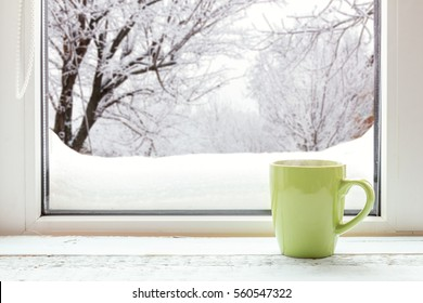 Cup of coffee on the window sill. In the background, a beautiful winter landscape in snow. Cozy home concept
