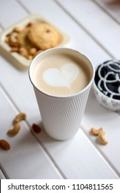 Cup of coffee on wood background with snacks. Heart in foam.