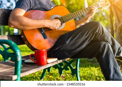 cup of coffee on wood bench near people play guitar in the park.