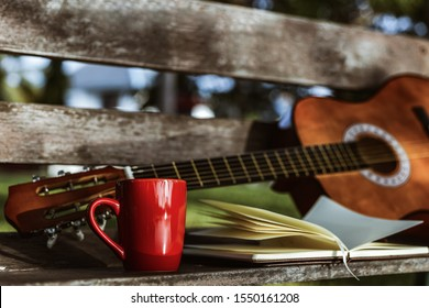 cup of coffee on wood bench near book and guitar.