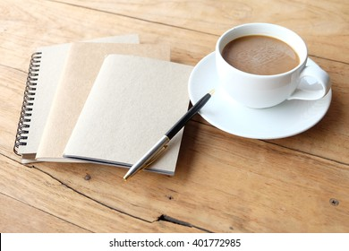 Cup of coffee on the wood with blank notebook