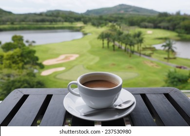 cup of coffee on the wood desk golf club background