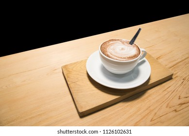 cup of coffee on wood table isolated on black background