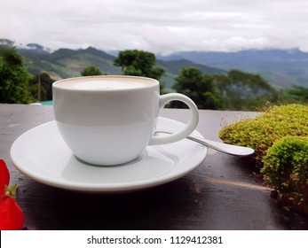 Cup coffee on wood table over mountains city landscape with sunlight. Beauty nature background. Lifestyle Concept