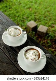 A cup of coffee on a wood table in a garden, very good time with friends, lovers or family to drink an aroma coffee in a romantic environment