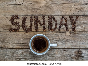 Cup of coffee on wooden background and SUNDAY coffee beans