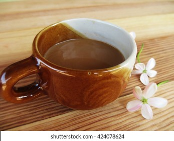 A cup of coffee on the wooden background