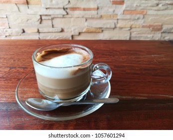 A cup of coffee on wooden table with brick wall background.