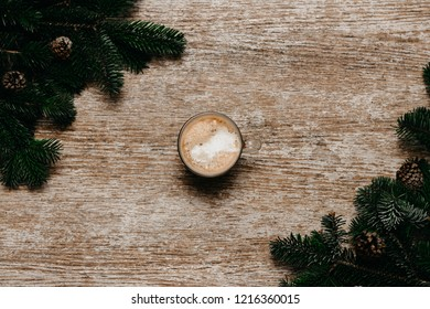 a cup of coffee on the wooden table beside spruce brunches. christmas concept. top view