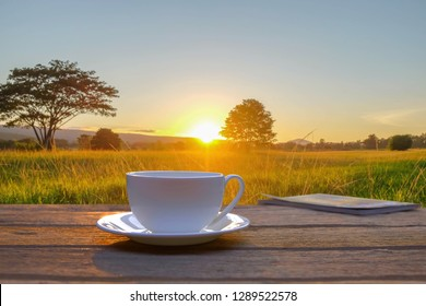 A cup of coffee on wooden table beside natural green grass field in the morning sunrise.