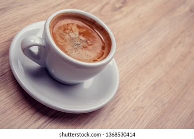 cup of coffee on wooden table from above