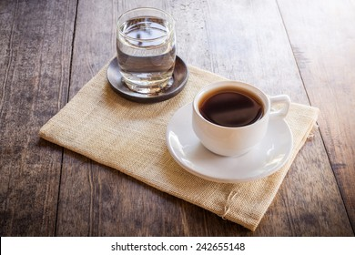 Cup of coffee on a wooden table with glass of water on the Sackcloth bags