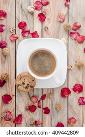 Cup of coffee on wooden table with petals of rose, view from above