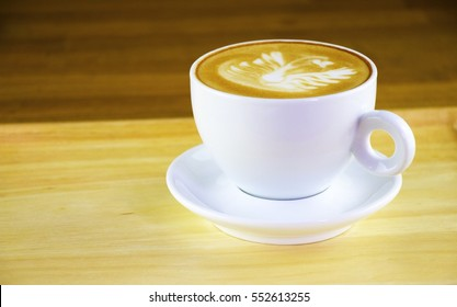 A cup of coffee is on wooden tray.