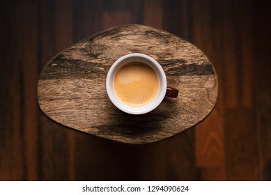 Cup of coffee on a wooden, vintage background. Mug of coffee on a cutting board with copy space. Vintage tones.