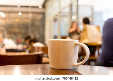 Cup of coffee with on wooend table in blur background