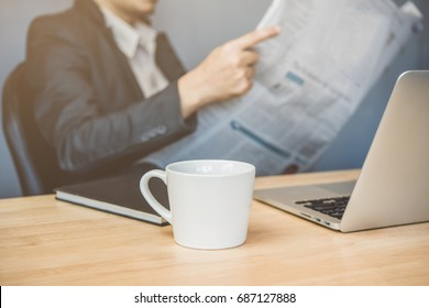 A cup of coffee on working table and business man reading newspaper.