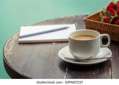 Cup of coffee and opened notebook on wooden table