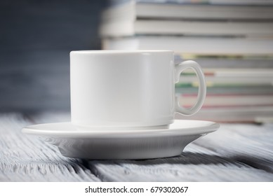 Cup of coffee over defocused pile of books