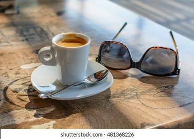 Cup of coffee and pair of glasses on vintage table. Soft focus wooden table with glasses, cup of coffee and spoon with sun beam.