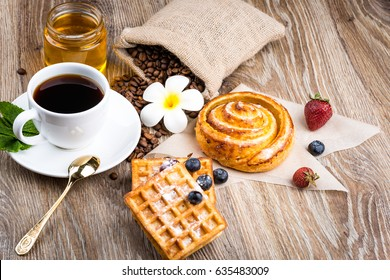 Cup of coffee and pastry on wooden background