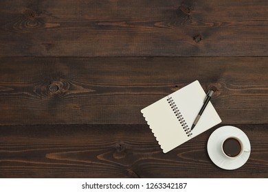 Cup of coffee, pen and open notebook on a wooden background. View from above.