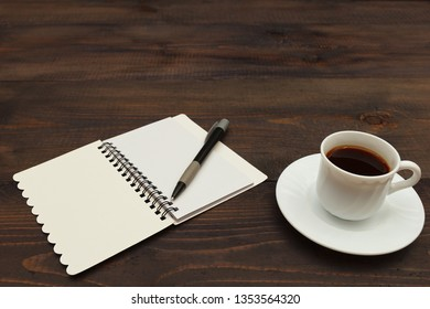 Cup of coffee, pen and open notebook on a wooden desktop