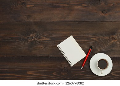 Cup of coffee, pen and pocketbook on a wooden desktop. View from above.