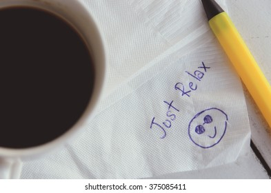 A cup of Coffee and pen with word  Just Relax  and emoticon smiling face handwriting on a napkin