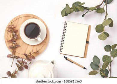Cup coffee, pencil, branch with leaf, paper note on white