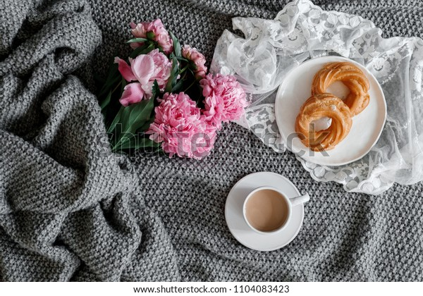 A cup of coffee and peonies on a gray background. Flat-lay of cup of coffee with  peonies