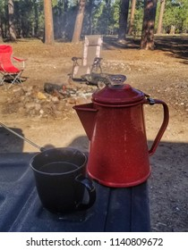 Cup of coffee and a percolator by a campfire