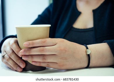 A cup of coffee, a phone, female hands on a table. Business, date, communication, recreation - concept, idea