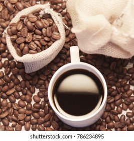 cup of coffee: photograph contains cup of black  fresh coffee, cofee beans and to creat ambiance jute bag.