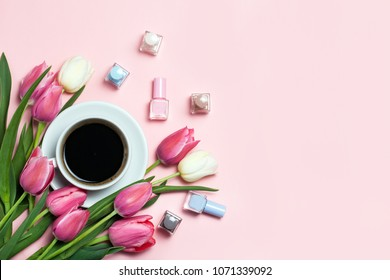 Cup of coffee, pink tulips and nail pilishes on pink background. Lovely greetings. top view, flat lay. beauty manicure concept.