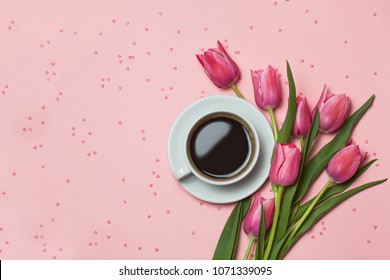 Cup of coffee, pink tulips on pink background. Lovely greetings. top view, flat lay.
