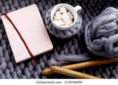 Cup of coffee and planner on in the cozy bed with gray blanket. Warm woolen yarn and knitting needle in the autumn or winter weekend, top view.