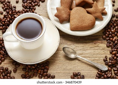 Cup of coffee and plate of gingerbread cookies on wooden background