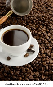 cup of coffee and pot on beans as background