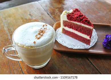 Cup of coffee and Red velvet cake on wooden table