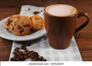 Cup of coffee with roasted coffee beans around and biscuit on cotton serviette on wooden  background