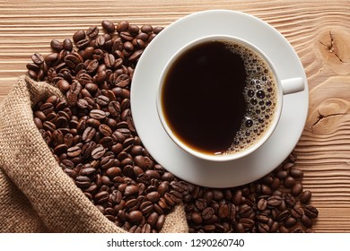 Cup of coffee with roasted beans on wooden table.