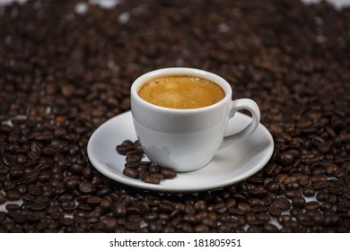 Cup of coffee with roasted coffee beans on the background.