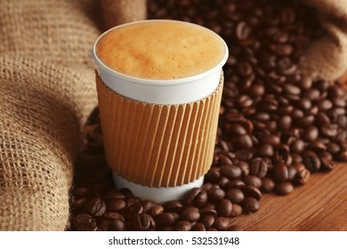 Cup of coffee with roasted beans on wooden table closeup