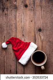 Cup of coffee and Santas hat on a wooden background, celebration
