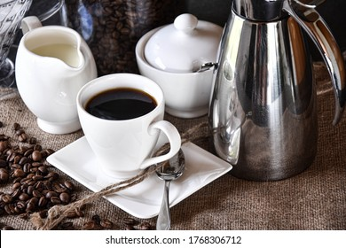 """Cup of coffee"" with saucer, milk jug, sugar bowl and thermos on a ""jute tablecloth"" with coffee beans - "" low angle shot"" from the front"