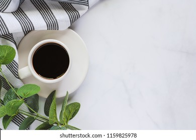 Cup of coffee with saucer, napery, leaf bouquet on white marble background for drinks and beverage concept