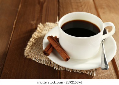 Cup of coffee with saucer, spoon and cinnamon on wooden table background