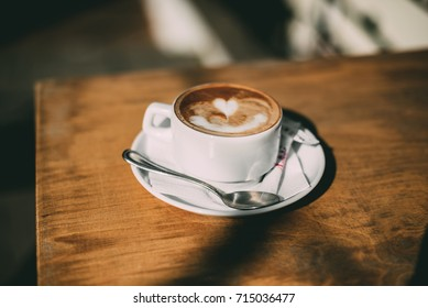 a cup of coffee with a saucer and a spoon stand on a wooden table